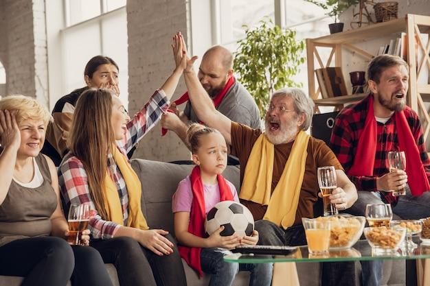 Podekscytowana, szczęśliwa duża rodzina oglądająca mecz piłki nożnej na kanapie w domu. fani dopingują emocjonalnie ulubioną drużynę narodową. zabawa od dziadków po dzieci. sport, telewizja, mistrzostwa.