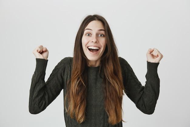 Podekscytowana szczęśliwa dziewczyna śpiewa, pompka pięścią z radości, wygrywa na loterii