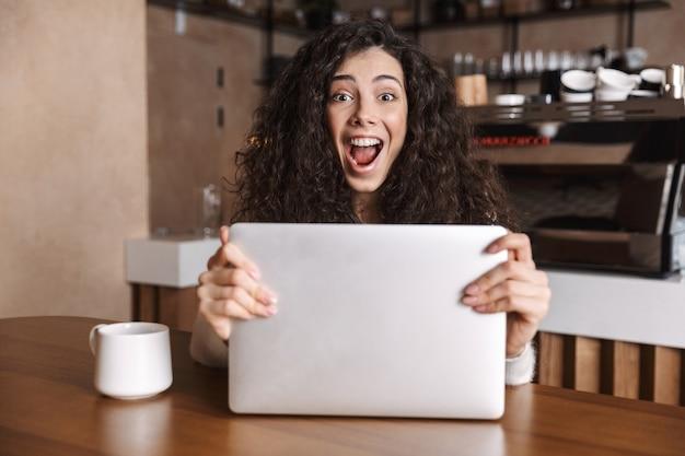 Podekscytowana szczęśliwa kobieta korzysta z laptopa, siedząc przy stoliku kawiarnianym i pijąc kawę