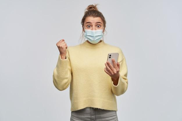 Podekscytowana, szczęśliwa kobieta o blond włosach zebranych w kok. noszenie żółtego swetra i ochronnej maski na twarz. trzyma smartfon i zaciska pięść. patrząc w kamerę, na białym tle nad białą ścianą