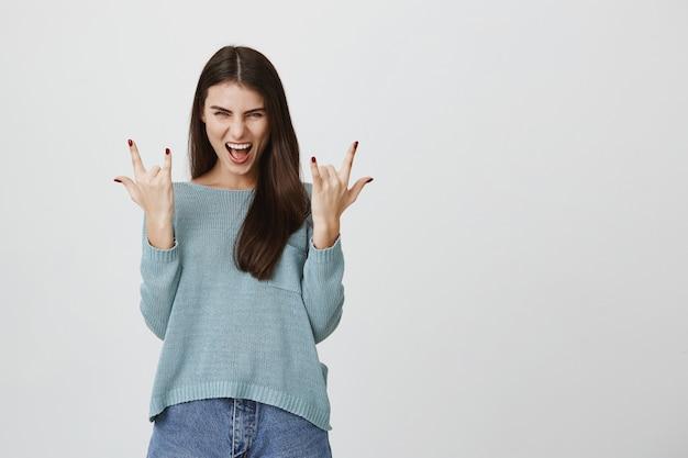 Podekscytowana szczęśliwa kobieta pokazuje znak rock-n-roll, dobrze się bawi
