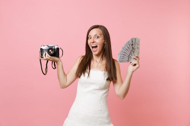 Podekscytowana szczęśliwa kobieta w białej sukni trzymaj retro vintage aparat fotograficzny pakiet dużo dolarów gotówki wybierając personel, fotograf