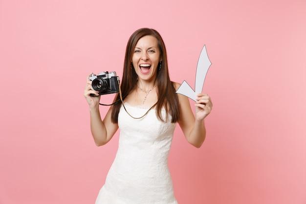 Podekscytowana szczęśliwa kobieta w białej sukni trzymająca retro vintage aparat fotograficzny i znacznik wyboru, wybierająca personel, fotograf