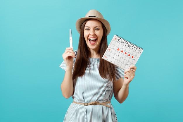 Podekscytowana szczęśliwa kobieta w niebieskiej sukience, kapelusz trzymaj w ręku test ciążowy, kalendarz okresów do sprawdzania dni menstruacji na białym tle na niebieskim tle. medycyna, opieka zdrowotna, koncepcja ginekologiczna. skopiuj miejsce.