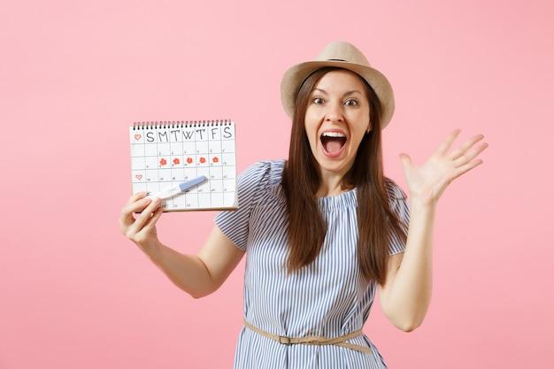 Podekscytowana szczęśliwa kobieta w niebieskiej sukience, kapelusz trzymaj w ręku test ciążowy, kalendarz okresów do sprawdzania dni menstruacji na białym tle na różowym tle. medycyna, opieka zdrowotna, koncepcja ginekologiczna. skopiuj miejsce.