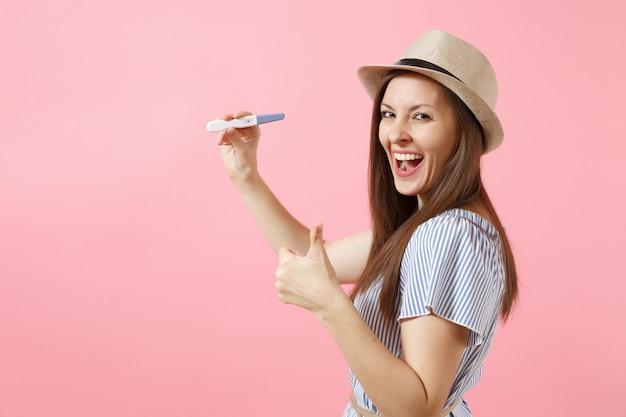 Podekscytowana szczęśliwa kobieta w niebieskiej sukience, trzymaj w ręku kapelusz, patrząc na test ciążowy na białym tle na różowym tle. medycyna opieki zdrowotnej ginekologiczne, koncepcja ludzie płodność ciąży macierzyństwa. skopiuj miejsce.
