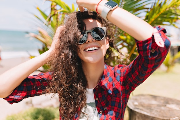 Podekscytowana szczęśliwa kobieta z falującymi włosami nosi okulary przeciwsłoneczne, wygląda na szczęśliwą i uśmiecha się. letnie wakacje