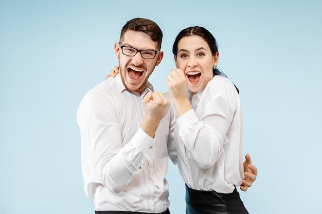 Podekscytowana szczęśliwa młoda para patrząc na kamery z zachwytem. biznesmen i kobieta na białym tle na niebieskim tle studio