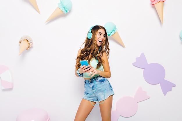 Podekscytowana szczupła dziewczyna z modnymi dodatkami i niebieskim telefonem bawi się na ozdobionej ścianie. portret opalonej kobiety w modnych dżinsowych szortach chłodzących się podczas słuchania muzyki w pokoju z cukierkami.