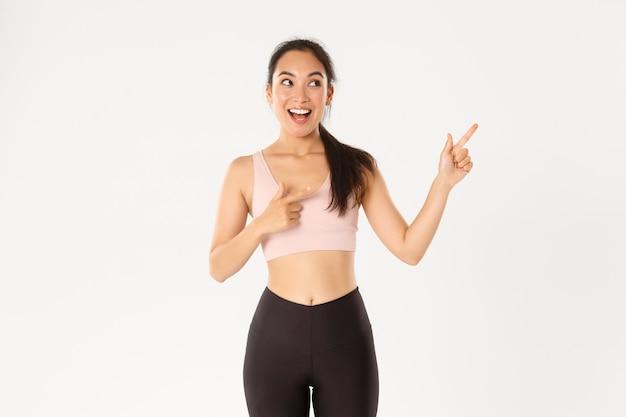 Podekscytowana szczupła i urocza azjatycka dziewczyna fitness, lekkoatletka wskazująca palcami w prawym górnym rogu, pokazująca promocję sprzedaży sprzętu do ćwiczeń lub ofertę siłowni.