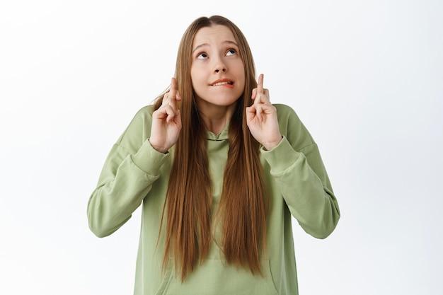 Podekscytowana urocza dziewczyna gryzie nerwowo wargę, krzyżuje palce i patrzy na copyspace, czekając na wyniki z zatroskaną miną, oczekując wiadomości, modląc się, stojąc nad białą ścianą