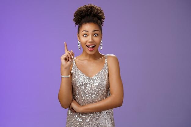 Podekscytowana urocza kreatywna afro-amerykańska dziewczyna znalazła odpowiedź podnosząc palec wskazujący eureka gest otwarte usta powiedzieć sugestia rozszerzać oczy zachwycona ciekawym pomysłem, niebieskim tłem.