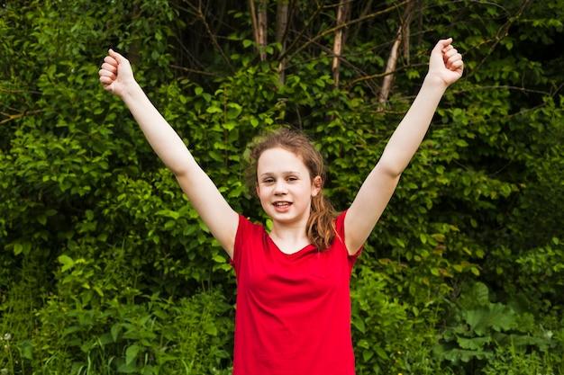 Podekscytowana uśmiechnięta dziewczyna podniósł ręce w geście sukcesu w parku