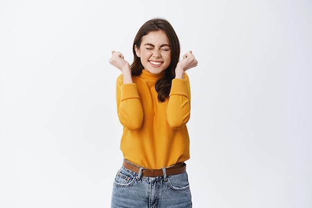 Podekscytowana uśmiechnięta dziewczyna wygrywa i świętuje, wesoło ściska ręce i skacze z radości, triumfuje, osiąga cel lub nagrodę, biała ściana