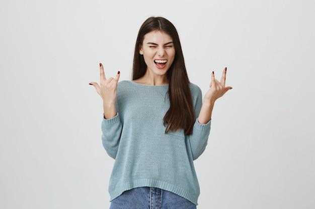Podekscytowana uśmiechnięta kobieta bawi się, pokazuje rock-n-rollowe znaki