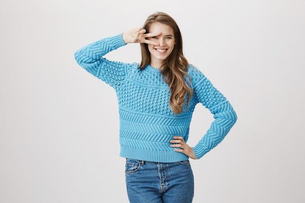 Podekscytowana uśmiechnięta kobieta pokazuje znak pokoju nad okiem