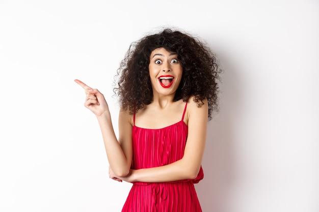 Podekscytowana Uśmiechnięta Kobieta Z Kręconymi Włosami I Makijażem, Ubrana W Elegancką Czerwoną Sukienkę, Krzycząca Zaskoczona I Wskazująca Palcem W Lewo Na Logo, Stojąca Na Białym Tle. Premium Zdjęcia