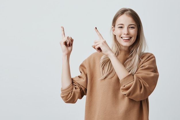 Podekscytowana wesoła europejka z długimi blond włosami, ubrana w ubranie i uśmiechająca się radośnie, wskazując palcami wskazującymi w górę