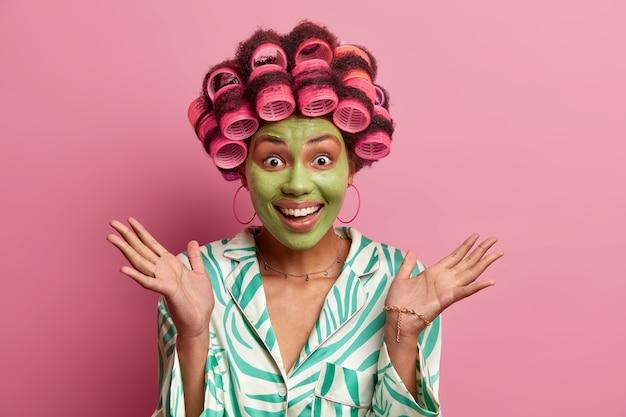 Podekscytowana wesoła kobieta rozkłada dłonie i pozytywnie chichocze dostaje od kosmetyczki niezłą radę jak dbać o skórę nakłada maseczkę upiększającą i wałeczki do włosów przygotowuje się na pierwszą randkę chce wyglądać pięknie
