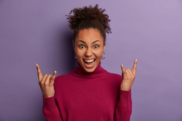 Podekscytowana, wesoła, kręcona kobieta rocker robi heavy metalowy znak, bawi się na niesamowitym koncercie rockowym, czuje się fajnie, ubrana w swobodny poloneck, wygląda na pewną siebie, pozuje w domu na fioletowej ścianie