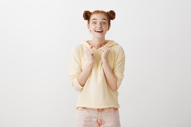 Podekscytowana wesoła ruda dziewczyna patrzy z pokusą i zainteresowaniem
