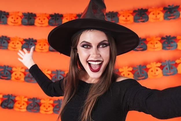 Podekscytowana wiedźma dziewczyna w czarnym kostiumie na halloween krzycząca do kamery na tle pomarańczowej ściany z dyni