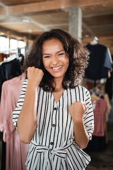 Podekscytowana właścicielka sklepu z modą w swoim butiku