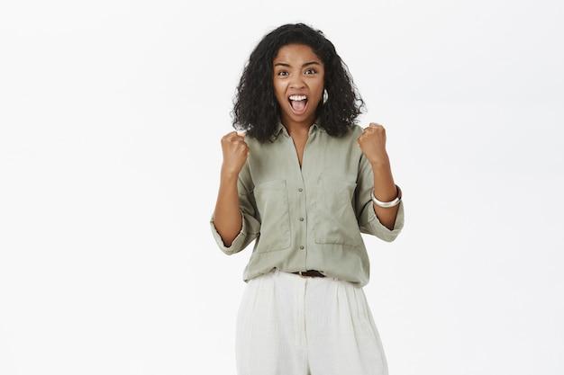 Podekscytowana wspierająca, energetyzowana ciemnoskóra kobieta z kręconymi włosami unosząca zaciśnięte pięści podczas wiwatu