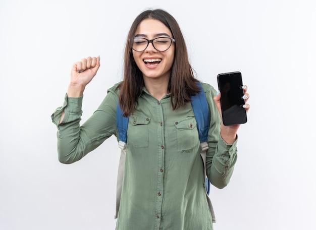 Podekscytowana z zamkniętymi oczami młoda uczennica w okularach z plecakiem trzymająca telefon pokazujący gest tak!