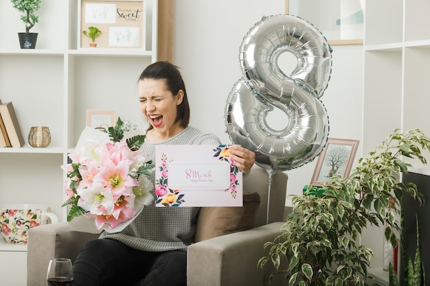 Podekscytowana z zamkniętymi oczami piękna kobieta w szczęśliwy dzień kobiet trzymająca bukiet z pocztówką siedząca na fotelu w salonie