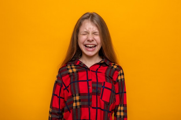 Podekscytowana z zamkniętymi oczami piękna mała dziewczynka ubrana w czerwoną koszulę odizolowaną na pomarańczowej ścianie
