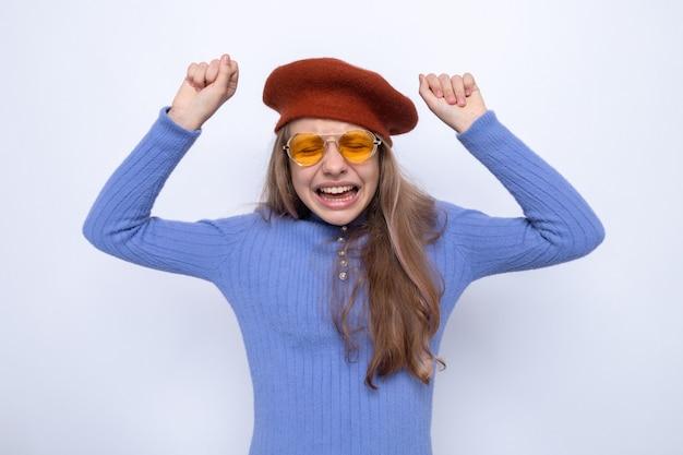 Podekscytowana z zamkniętymi oczami pokazująca gest tak piękna mała dziewczynka w okularach z kapeluszem odizolowana na białej ścianie
