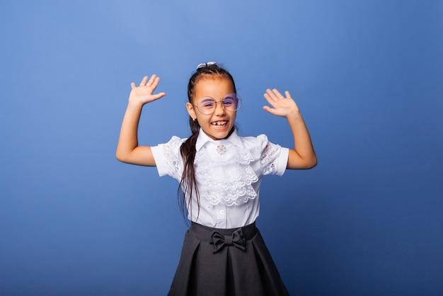 Podekscytowana, zaskoczona mała uczennica uśmiecha się z podniesionymi rękami na niebieskim tle na białym tle żółty kolor tła