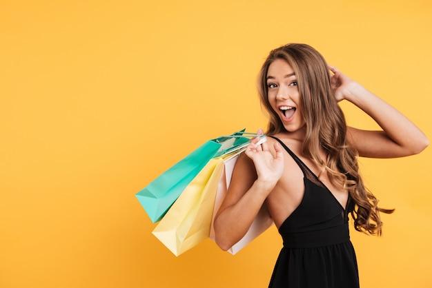 Podekscytowana zaskoczona młoda dama trzyma torby na zakupy.