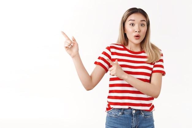 Podekscytowana zdziwiona młoda azjatycka dziewczyna blond krótka fryzura dysząca składane usta rozbawiona wyskakujące oczy kamera wskazująca górny lewy róg zdziwiona pytana rozmawiająca przyjaciółka, biała ściana