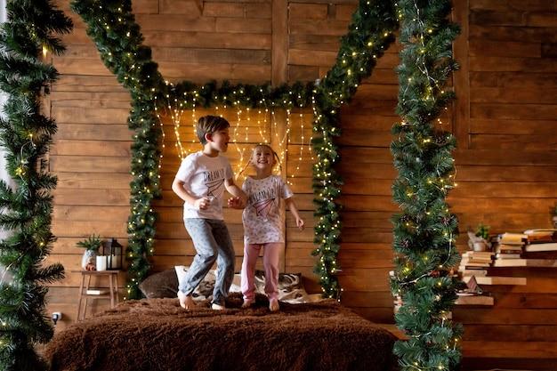Podekscytowane dzieci skaczące na łóżku rodziców w domu jako rodzina otwarte prezenty w boże narodzenie