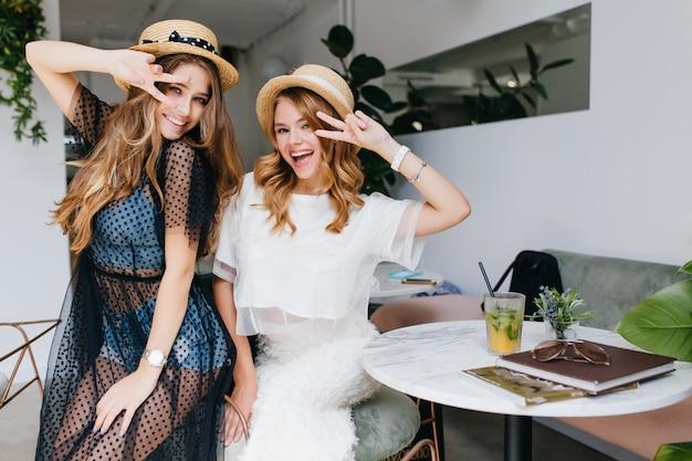 Podekscytowane dziewczyny w podobnych słomkowych kapeluszach pozujące ze znakiem pokoju, śmiejące się i wygłupiające się