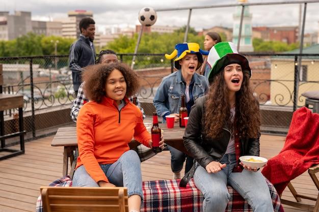 Podekscytowane dziewczyny z piwem i przekąskami kochające swoją drużynę piłkarską z chłopakami
