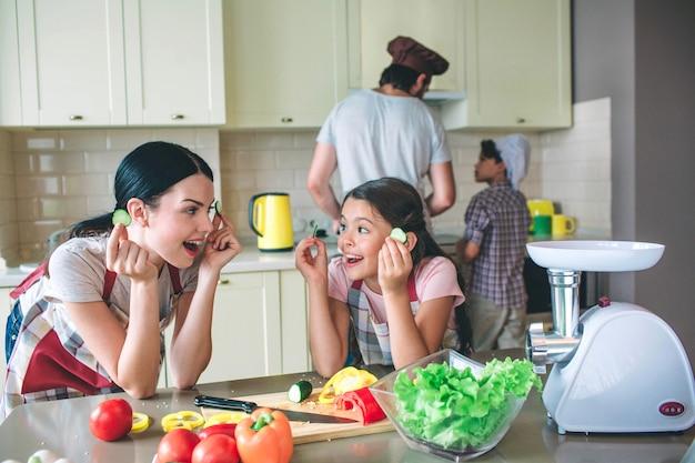Podekscytowane i szczęśliwe dziewczyny pochylają się do stołu i patrzą na siebie. bawią się okrągłymi kawałkami ogórka. dziewczyny mają przerwę. chłopcy śpiewają razem przy kuchence za młodymi kobietami.