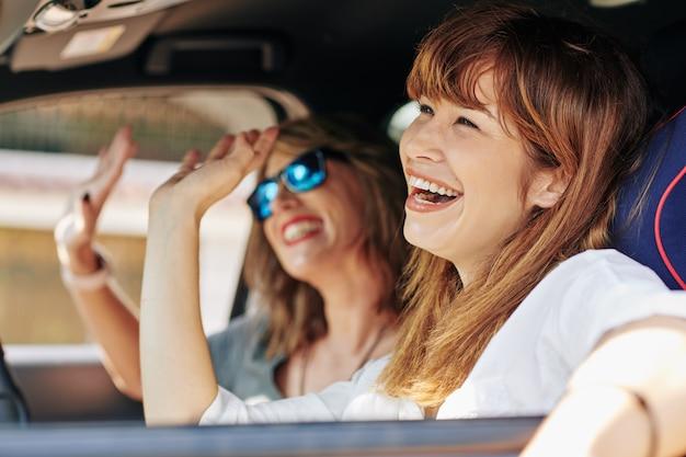 Podekscytowane kobiety jeżdżące w samochodzie