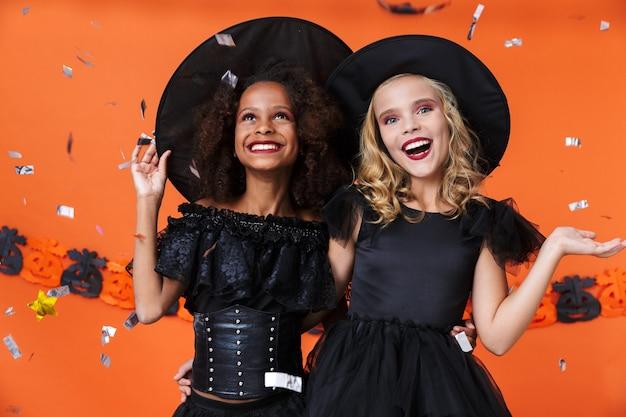 Podekscytowane kobiety wiedźmy w czarnych kostiumach na halloween, uśmiechnięte i przytulające się razem na białym tle nad pomarańczową ścianą z dyni