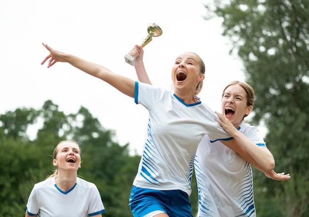 Podekscytowane kobiety z pucharami zwycięzców
