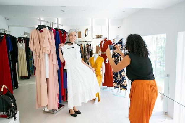 Podekscytowane koleżanki, ciesząc się razem zakupy w sklepie mody, trzymając sukienkę i robienie zdjęć na telefonie komórkowym. koncepcja konsumpcjonizmu lub zakupów