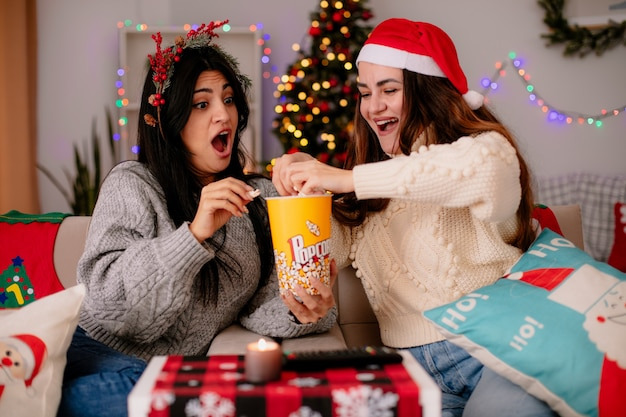 Podekscytowane ładne młode dziewczyny w czapce mikołaja i wieńcu ostrokrzewu trzymają i patrzą na wiadro popcornu siedząc na fotelach i ciesząc się świętami w domu