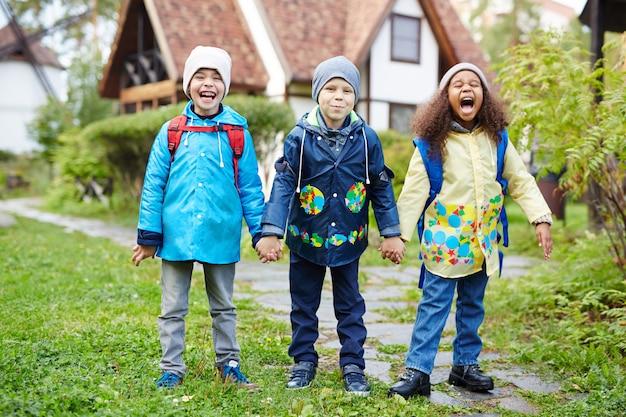 Podekscytowane małe dzieci chodzą do szkoły