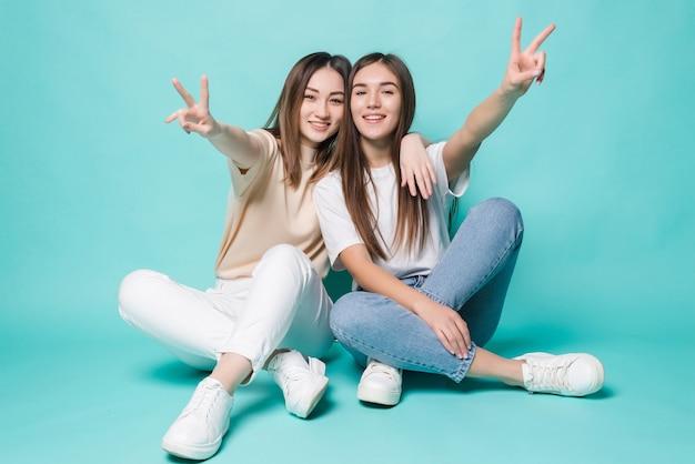 Podekscytowane młode kobiety z pokojem, pozowanie na podłodze na białym tle na turkusowej ścianie.