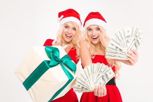 Podekscytowane piękne siostry bliźniaczki w strojach świętego mikołaja i kapeluszach pokazujące pieniądze i prezent na białym tle