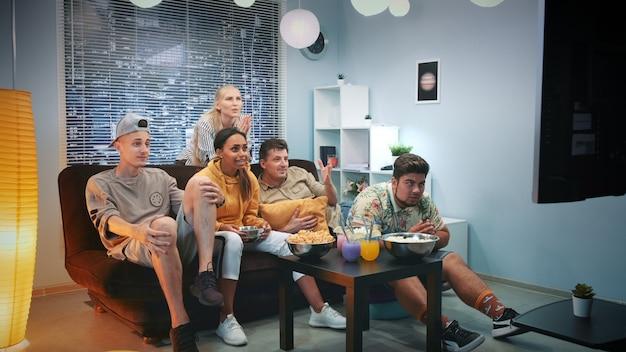 Podekscytowani fani oglądają sport w telewizji i rozlewają popcorn, gdy drużyna zdobywa bramki