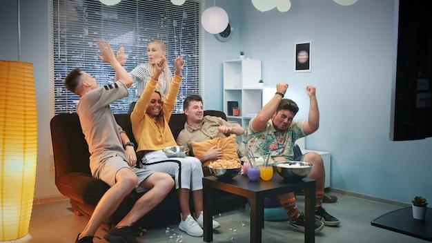 Podekscytowani fani oglądają sport w telewizji i rozlewają popcorn