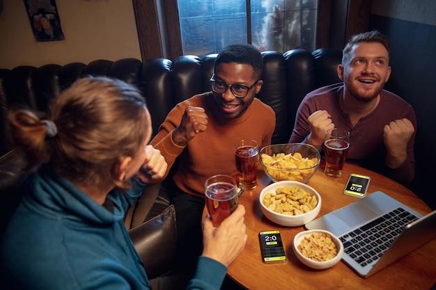 Podekscytowani fani z aplikacją mobilną do obstawiania i zdobywania punktów na swoich urządzeniach hazardowych emocji